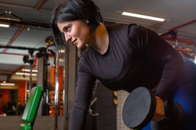 Una bella giovane atleta femminile in una giacca sportiva nera fa un esercizio con manubri in palestra.