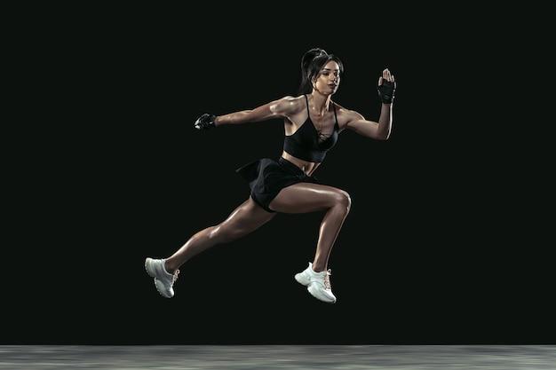Bella giovane atleta femminile che pratica su sfondo nero studio, ritratto a figura intera. modello bruna in forma sportiva in corsa, salto. body building, stile di vita sano, concetto di bellezza e azione.