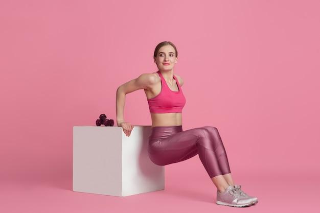 Bello giovane atleta femminile che si esercita sul ritratto monocromatico della parete rosa