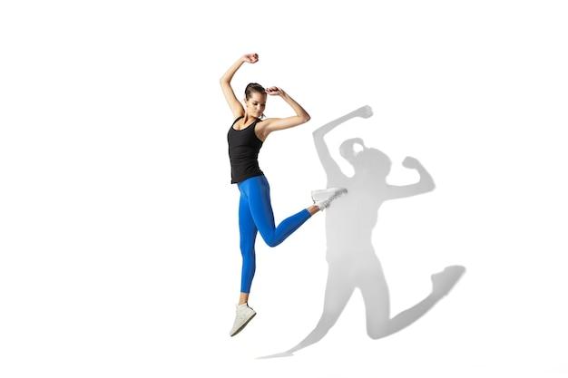 Bella giovane atleta femminile che allunga sul fondo bianco dello studio con le ombre