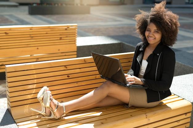 Bella giovane femmina su una panchina in estate con un computer portatile