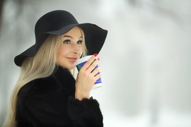 Bella giovane femmina in un cappotto di pelliccia nera e cappello in inverno in una passeggiata con una tazza di caffè