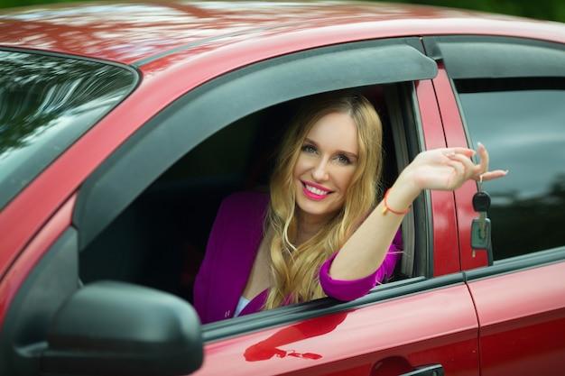 Bella giovane femmina in una macchina con le chiavi