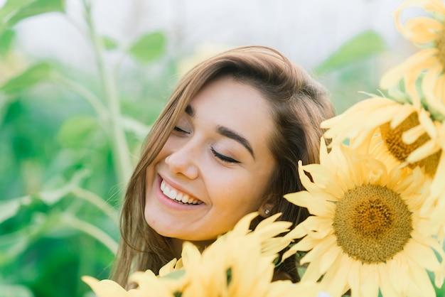 Bella giovane femmina per godersi la natura sul campo di girasoli al tramonto