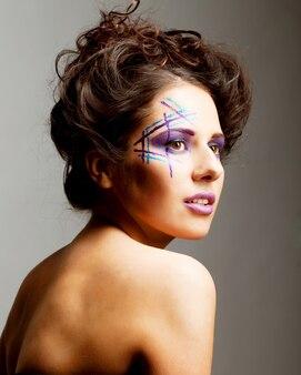 Bel giovane volto femminile con trucco multicolore di moda brillante