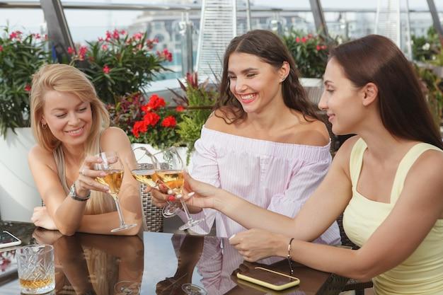 Belle giovani amiche che celebrano insieme al bar sul tetto, tintinnanti bicchieri di vino