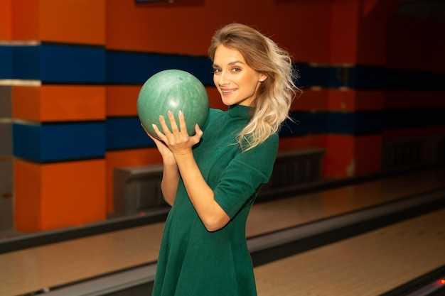 Bella giovane donna che gioca a bowling