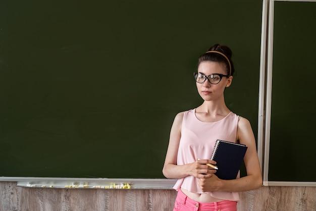 Bella giovane insegnante o studentessa in piedi vicino alla lavagna vuota