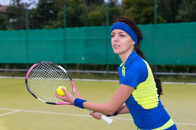 Bella giovane tennista che serve indossando un abbigliamento sportivo durante una partita di tennis sul campo da tennis in erba all'aperto in estate o in primavera