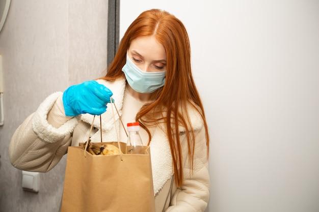 Bella giovane donna volontaria con i capelli rossi consegna la spesa a casa