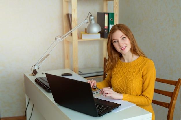 Bella giovane femmina al lavoro con il computer portatile