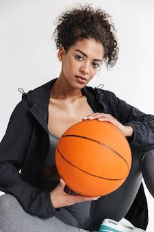 Bella giovane sportiva africana in forma isolata su un muro bianco, che tiene pallacanestro