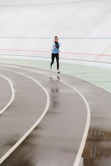 Bella giovane sportiva africana sicura di forma in forma che corre allo stadio