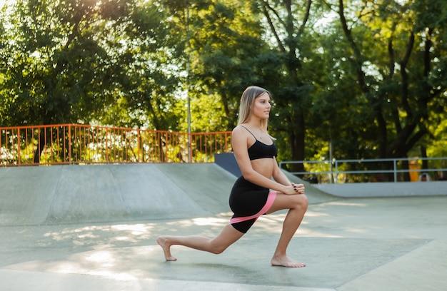 Bella giovane donna in forma che fa esercizio mattutino con elastici fitness all'aperto.