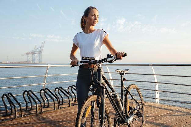 Bella giovane ragazza fitness in piedi all'aperto con una bicicletta, paesaggio marino