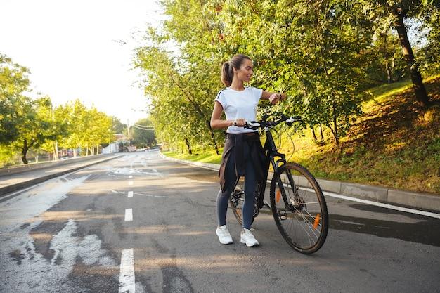 Bella giovane ragazza di forma fisica che cammina con la bicicletta sulla strada del parco