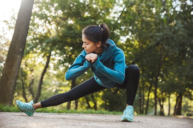 Bella giovane donna di forma fisica che fa esercitazione mattutina al parco