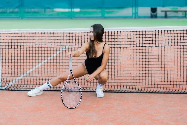 Ragazza sexy fitness bella giovane sport libero vestita in tuta su un campo da tennis