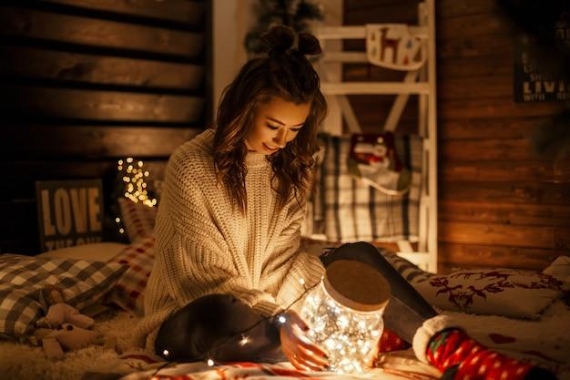 Bella giovane ragazza divertente con un sorriso in un maglione lavorato a maglia con un barattolo magico con luci natalizie sul letto