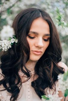 Bella ragazza sullo sfondo di un giardino fiorito. avvicinamento