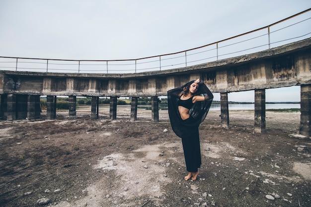 Bella ragazza sullo sfondo della diga in un lago prosciugato con la gonna nera oscillante