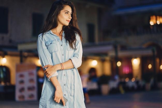 Una bella ragazza in un abito blu in piedi in una città di notte con il telefono