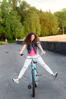 Bella ragazza in abiti casual a riposo e in bicicletta in estate in città lungo l'argine