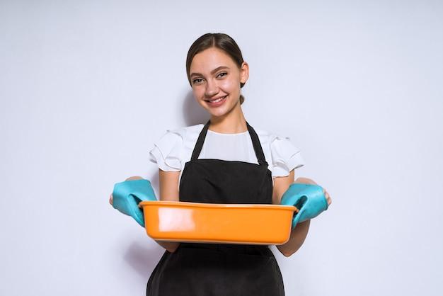 Cuoco della bella ragazza che prepara la torta nel forno, cuocendo al forno