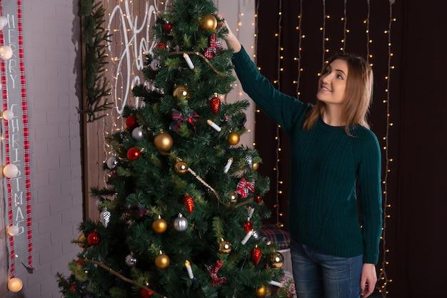 La bella ragazza decora un albero di natale