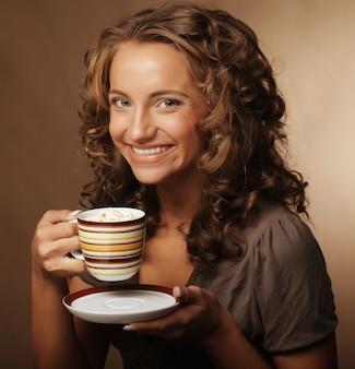 Bella ragazza che beve tè o caffè