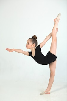 Bella ragazza impegnata nella ginnastica su un muro bianco