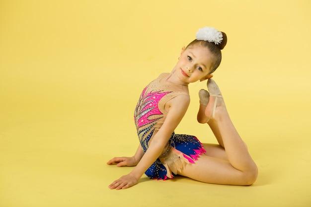 Bella ragazza impegnata nella ginnastica su un muro giallo