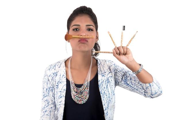 Bella ragazza che gode con i pennelli di trucco isolati su bianco