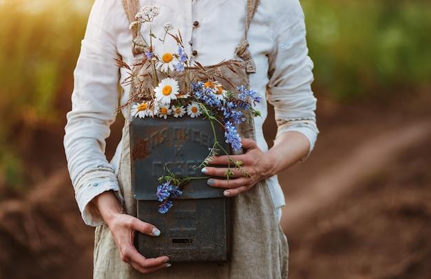 La bella ragazza in un campo di fiori gode del profumo e della vista delle margherite di campo