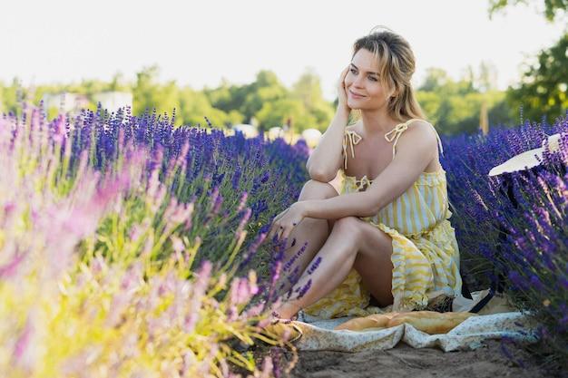 Bella e giovane ragazza in un campo pieno di fiori di lavanda