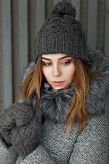 Bella ragazza in un cappello lavorato a maglia grigio e guanti vicino alla parete di legno