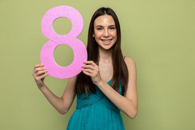 Bella ragazza sulla felice festa della donna che tiene il numero otto