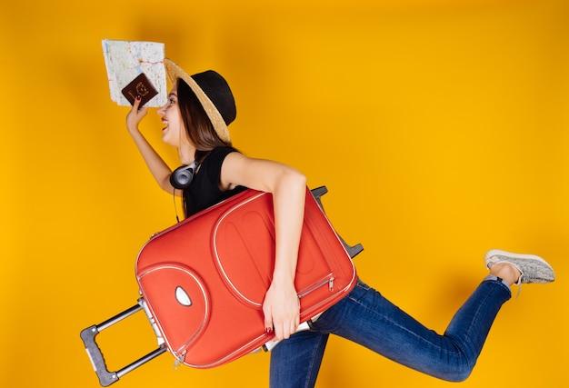 La bella ragazza con un cappello va in viaggio, in vacanza, con una grande valigia