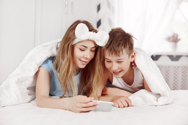 Una bella ragazza e suo allegro fratello minore guardano le foto sul telefono mentre giacciono sul letto con un sorriso
