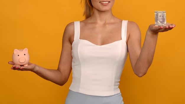 Bella ragazza che tiene un salvadanaio di maiale e 100 dollari su sfondo giallo. per risparmiare ricchezza di denaro e concetto finanziario.- immagine