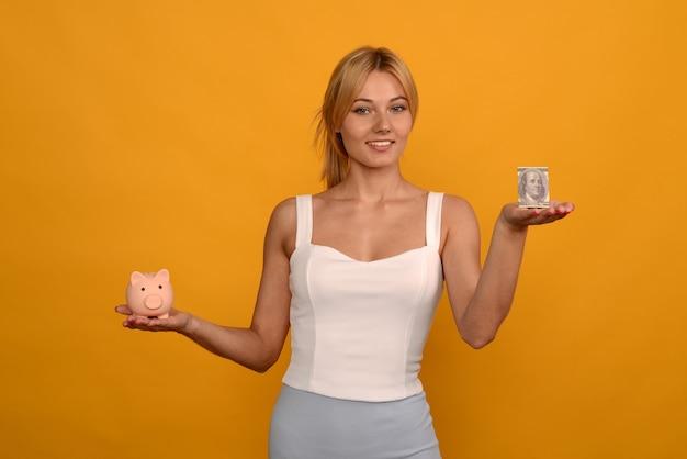 Bella ragazza che tiene un salvadanaio di maiale e un dollaro su sfondo giallo. per risparmiare ricchezza di denaro e concetto finanziario.