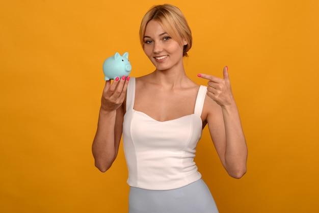 Bella ragazza che tiene un salvadanaio di maiale e puntare il dito su sfondo giallo. per risparmiare ricchezza di denaro e concetto finanziario.