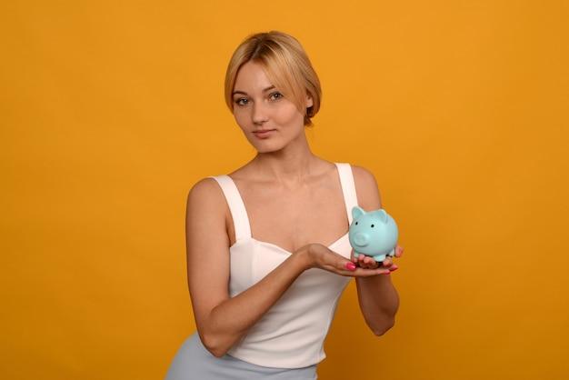 Bella ragazza che tiene un salvadanaio di maiale su sfondo giallo. per risparmiare ricchezza di denaro e concetto finanziario.