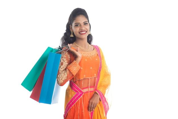 Bella ragazza che tiene i sacchetti della spesa mentre indossa l'usura etnica tradizionale su bianco