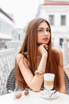 Bella ragazza sta bevendo un delizioso latte in un caffè estivo
