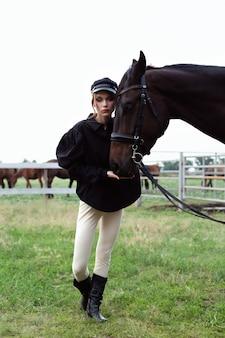 Una bella ragazza tiene un cavallo per le redini