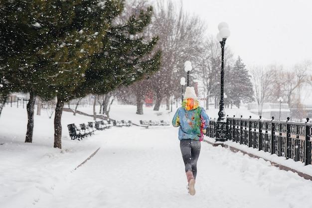 Una bella ragazza sta facendo jogging in una giornata gelida e nevosa. sport, stile di vita sano.