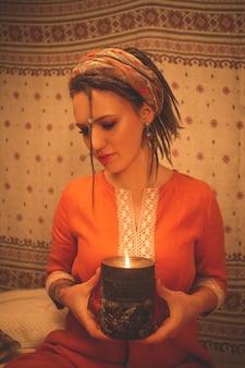 Una bella ragazza è seduta in una posa di yoga e meditazione con una candela in mano