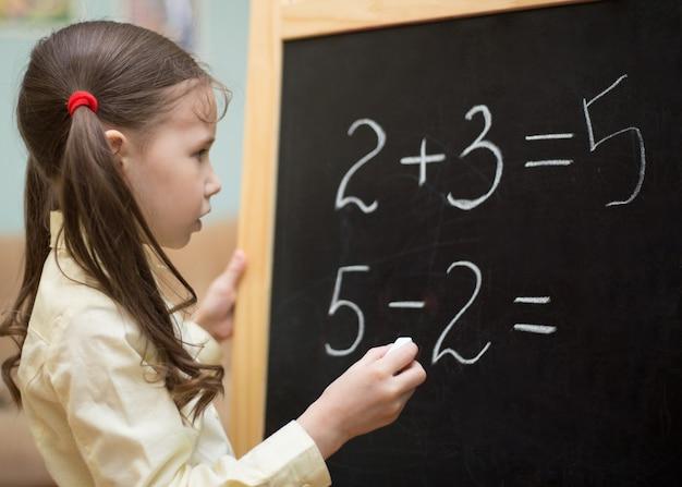 La bella ragazza sta insegnando a casa sulla lavagna