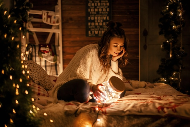 Bella ragazza in un maglione lavorato a maglia con un barattolo magico con luci sul letto.